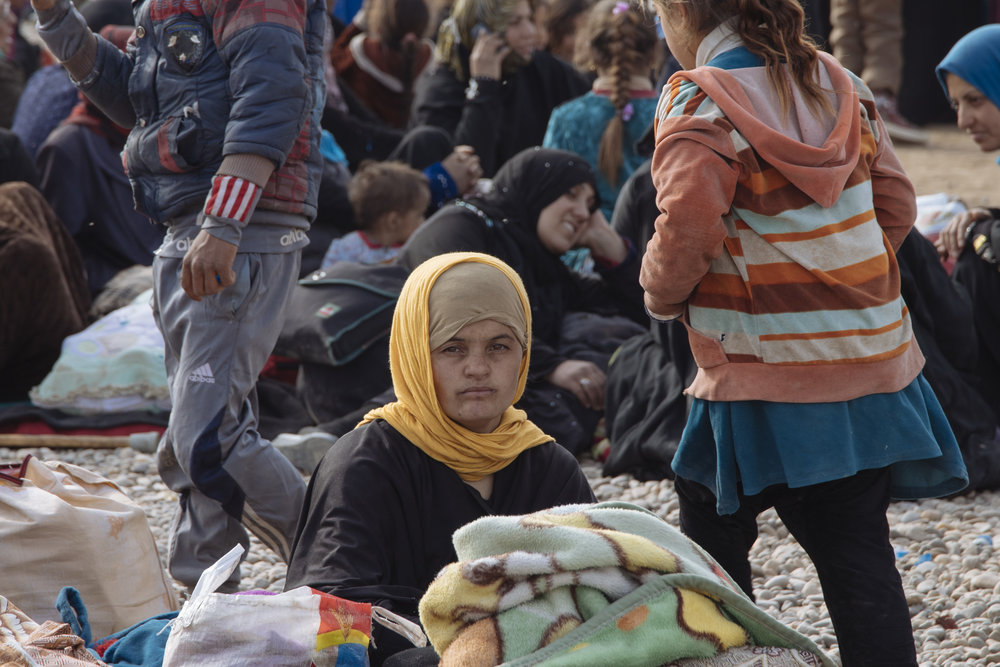A young girl who just arrived to the camp waiting for her family members.