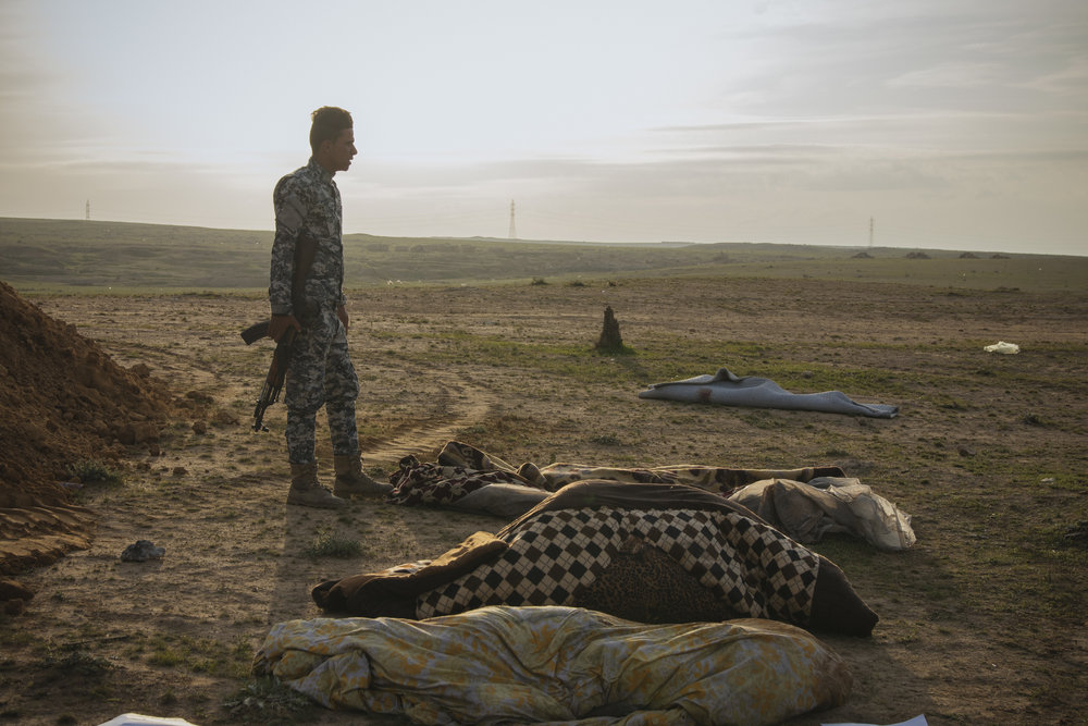 Iraqi Security personnel helps reburied bodies found in a mass grave left by ISIS.