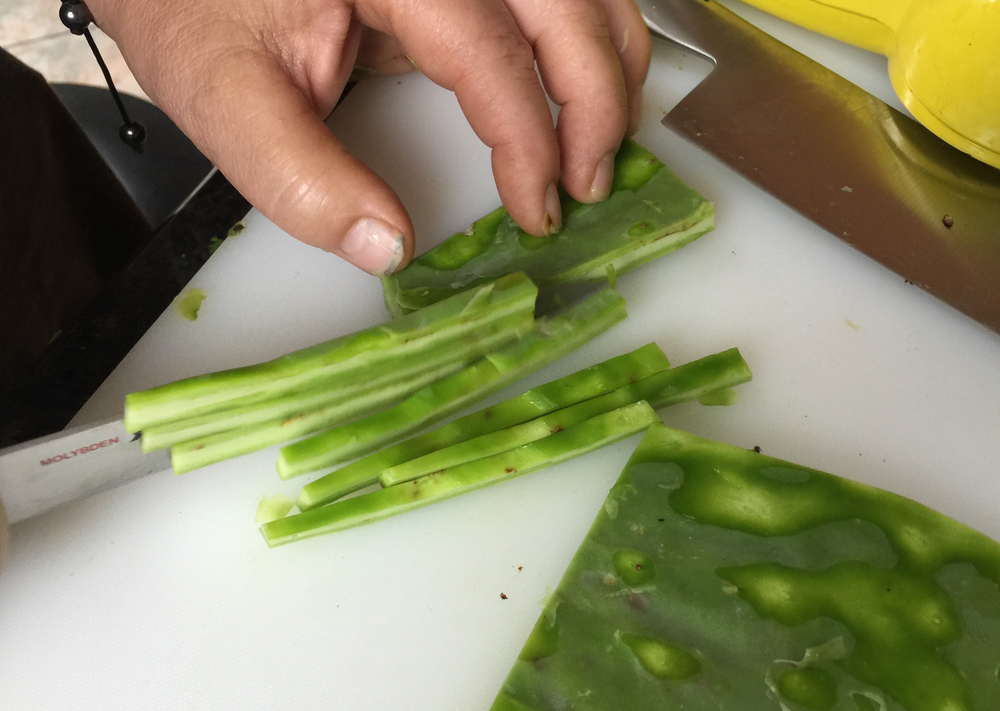 Monica slices nopal – a cactus paddle – before boiling it.