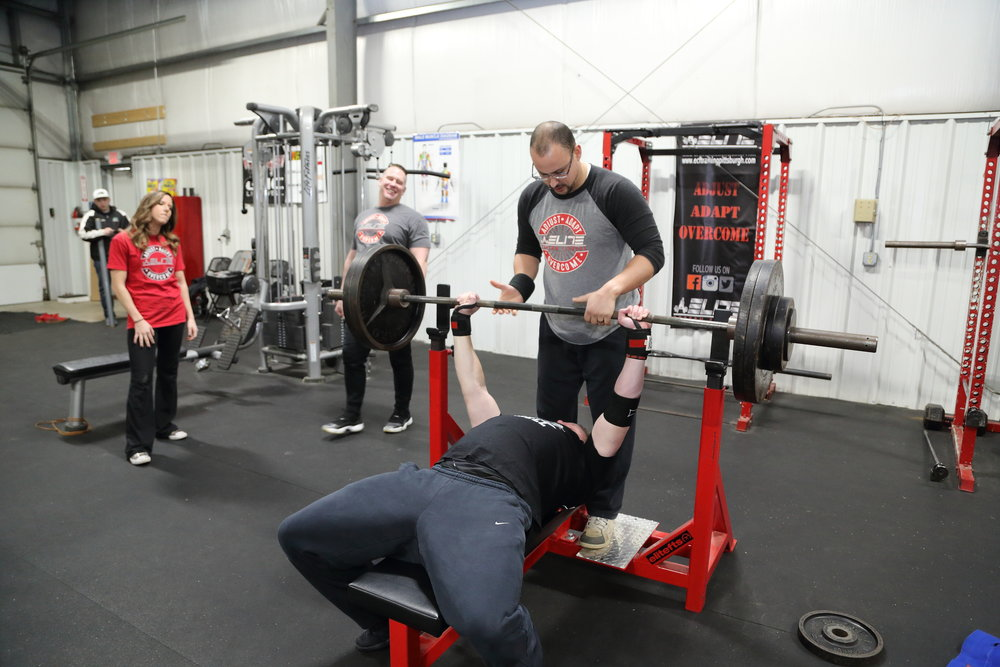 Captured here, Tim is assisting with one of our guys group classes on working toward building strength on the bench press.