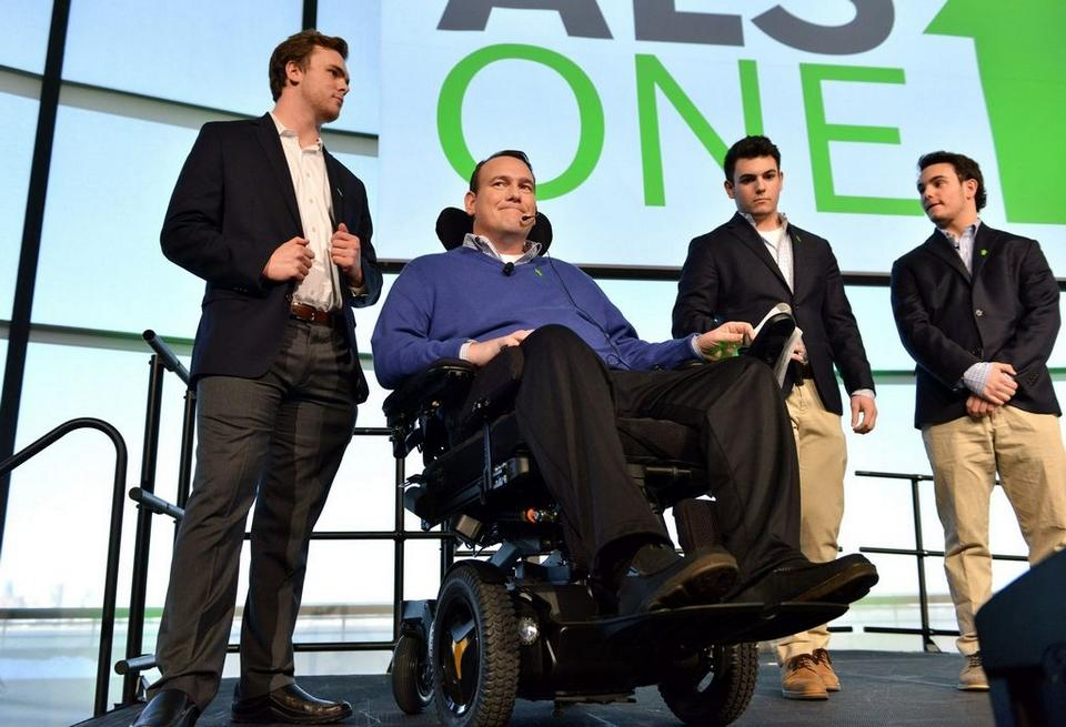 Kevin Gosnell, center, founder of the ALS Knights and person living with ALS, was joined on stage by his sons, from left, Scott, Jake and Joey Gosnell to celebrate the launch of his new initiative, ALS ONE, at the John F. Kennedy Library in Boston, Thursday, Jan. 21. (Credit: Josh Reynolds/AP Images)