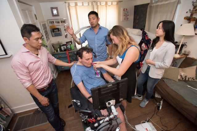 Dexter Ang, left, rests a hand on the back of Bobby Forster, who sips water held by his wife, Casey. Behind them, David Cipoletta, a robotics engineer, tests the sensitivity of the EMG sensors. Wenxin Feng looks on.  Photo: Gretchen Ert/School of Engineering