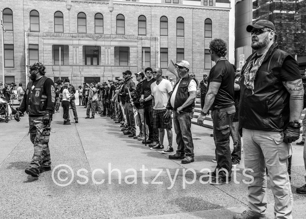 WCAI members (also members of Soldiers of Odin) line the front of Calgary City Hall while speakers emerge from behind.