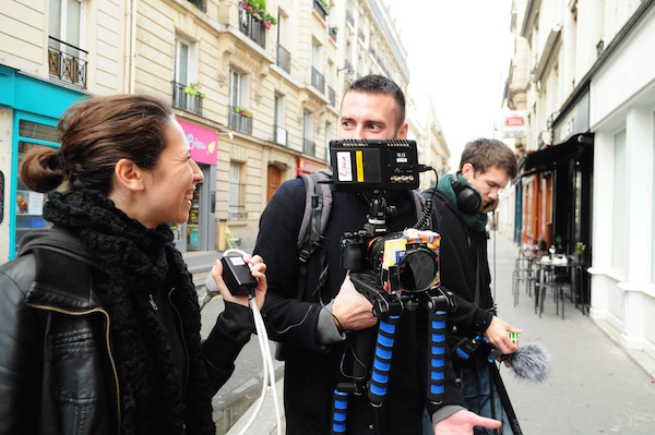 Selen P. Flores shares a laugh with Bruno Guillard on set of Margot in Paris, France. Image by:Nico Paprota