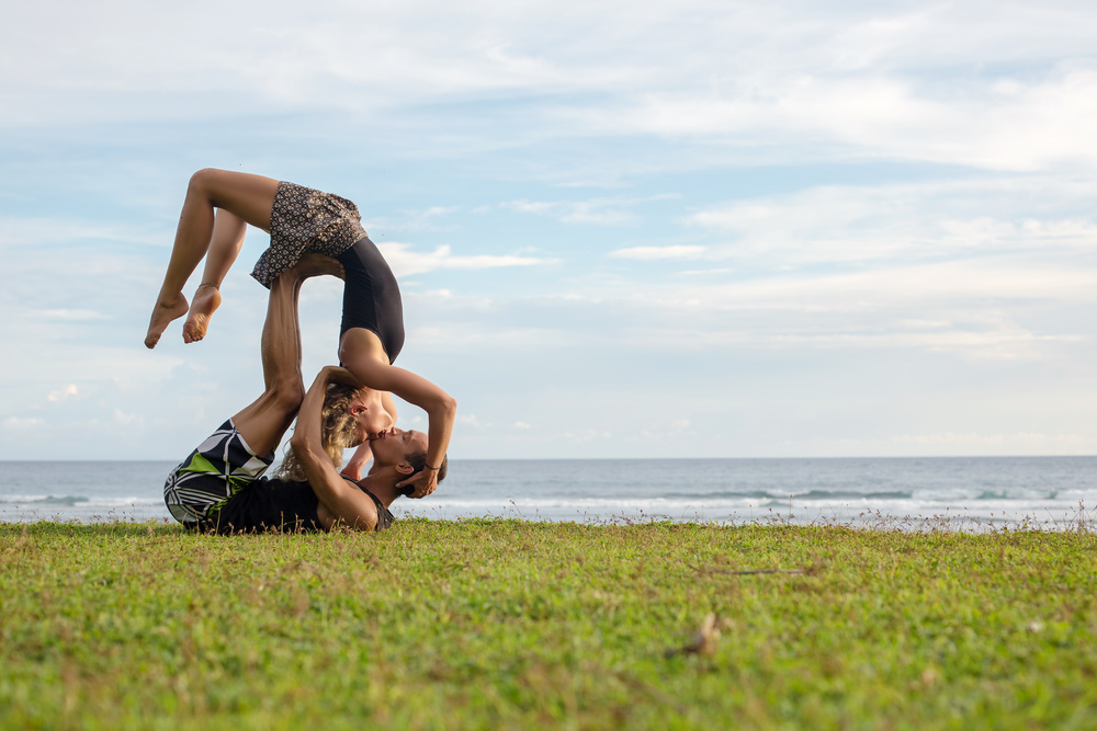 Love beautiful couple on the beach doing dancing fitness yoga exercise together. Valentine day love beautiful