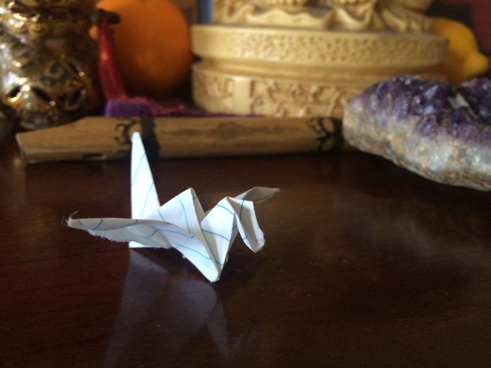 Origami with three intentions written inside placed by a feng shui inspired altar. Intentions could be written on a flat piece of paper or creatively constructed.