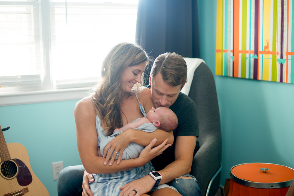 parents cradling newborn in family portrait session Wilmington nc