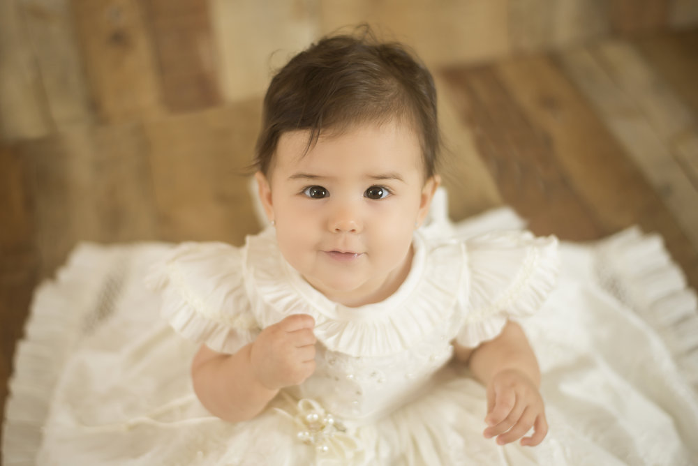 baby girl wearing white christening gown looks up at camera