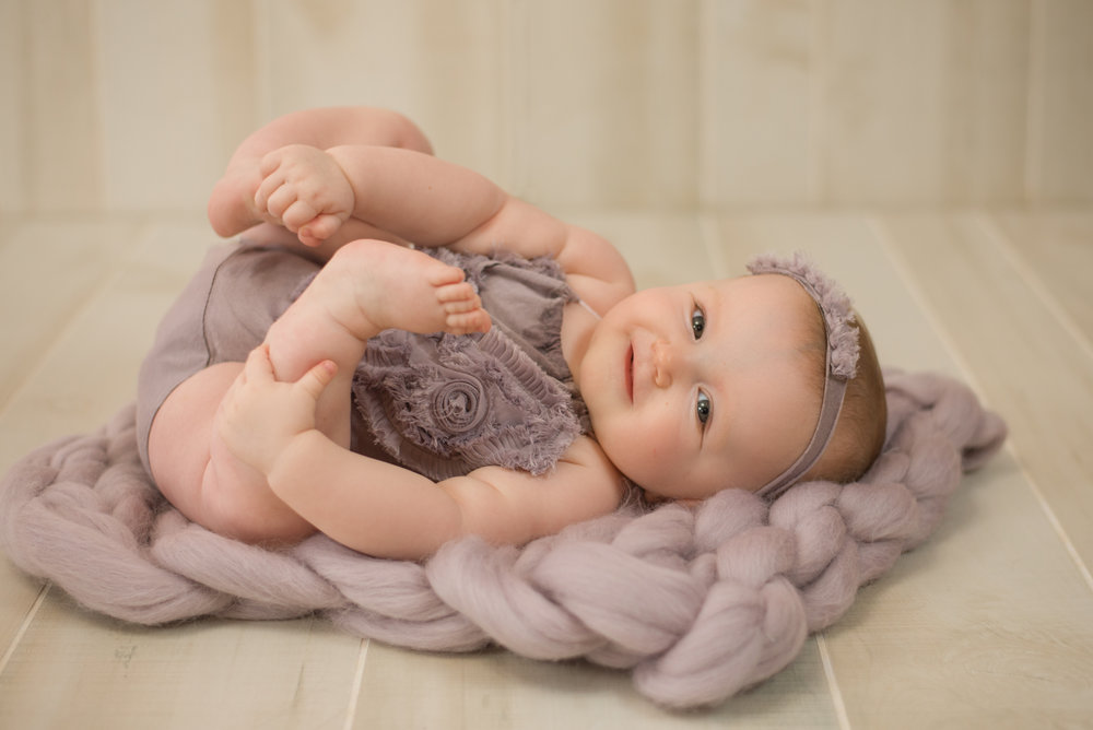Wilmington nc photographer captures baby girl reaching for toes on purple fluff