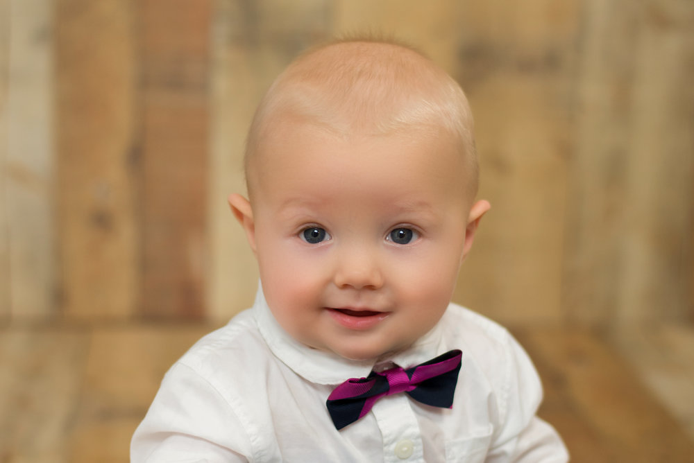 Wilmington nc photographer captures baby smiling while wearing a bow tie