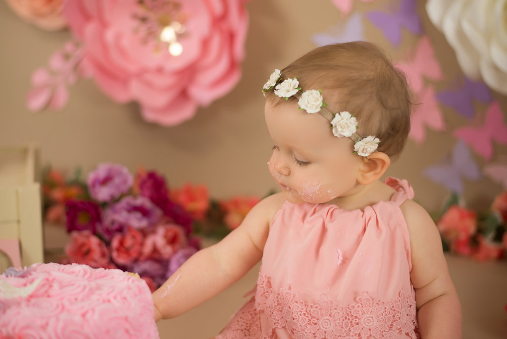 baby girl wearing pink eats cake surrounded by flowers during cake smash in Wilmington nc