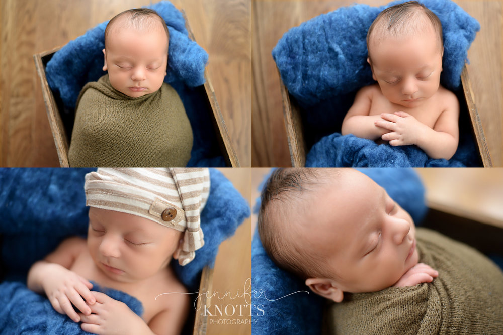 newborn boy posed in wooden box stuffed with blue fluff