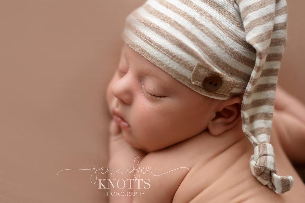 newborn boy wearing sleepy cap while posed with hand under cheek