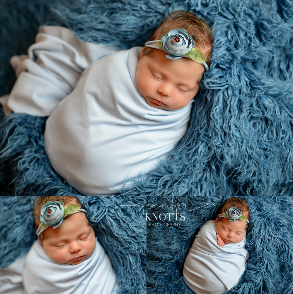 baby girl sleeps in blue fur wearing flower headband during Wilmington newborn session