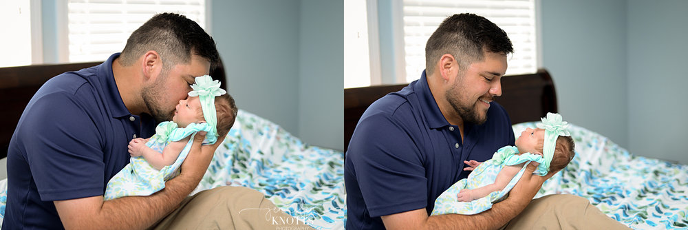 dad kisses newborn daughter on bed