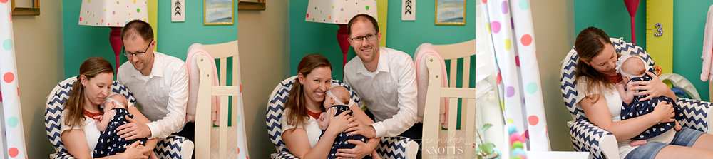 parents cuddle newborn girl in brightly colored nursery