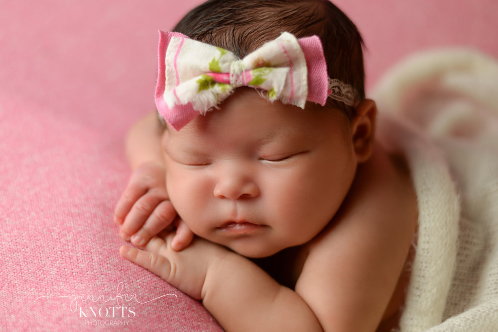 newborn girl on pink fabric wearing bow rests her face on hands