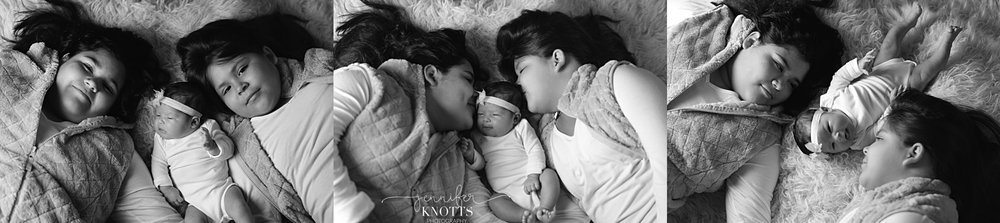 two older sisters pose with newborn baby girl