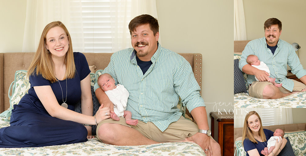 mom and dad hold newborn baby girl on bed wearing navy and greens