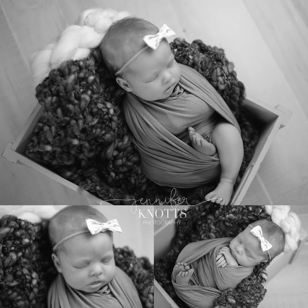 black and white images of newborn girl sleeping in wooden box while wearing rainbow headband