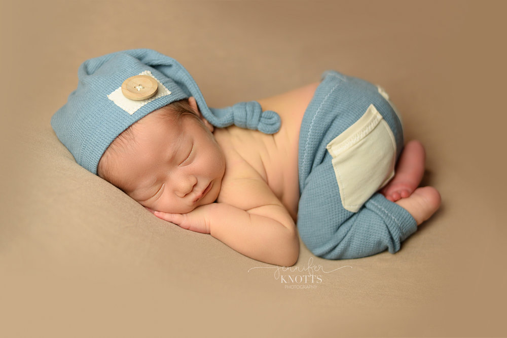 baby boy sleeps on tan blanket wearing blue outfit and hat