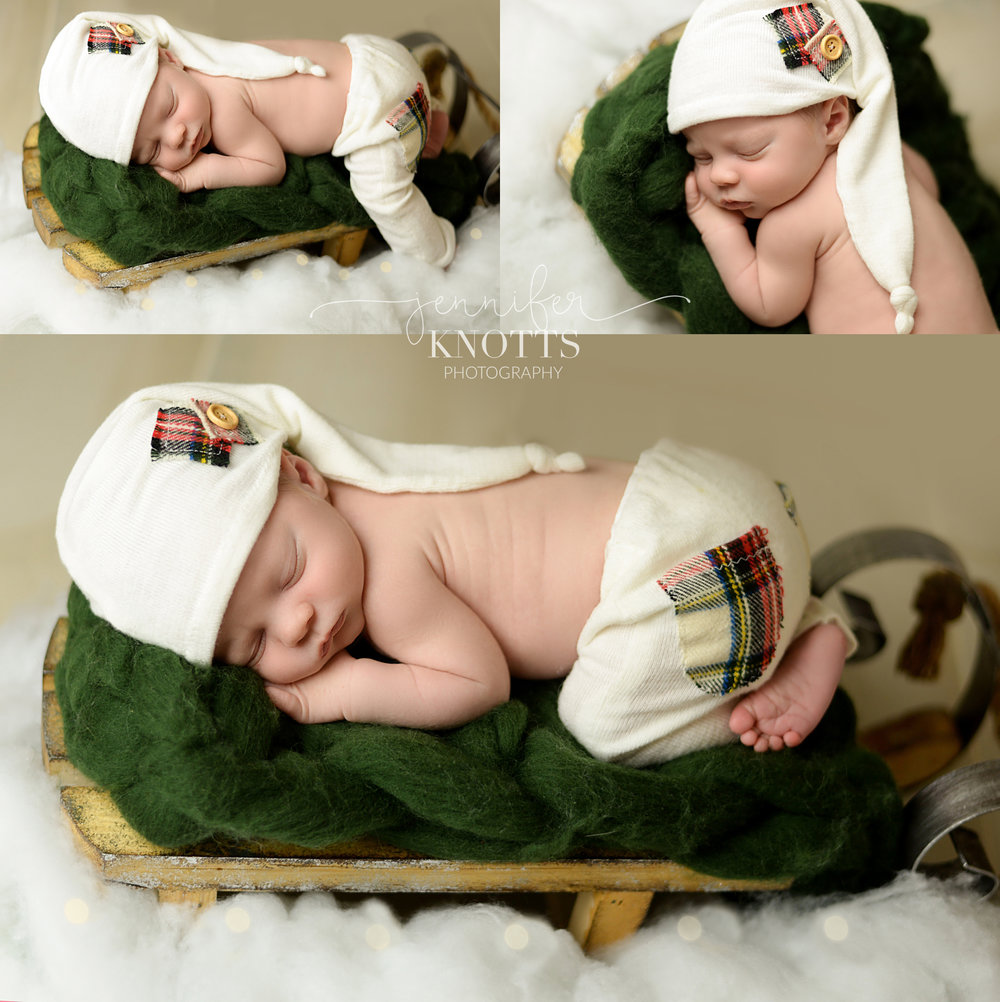 baby boy sleeps on sled prop wearing white hat and outfit