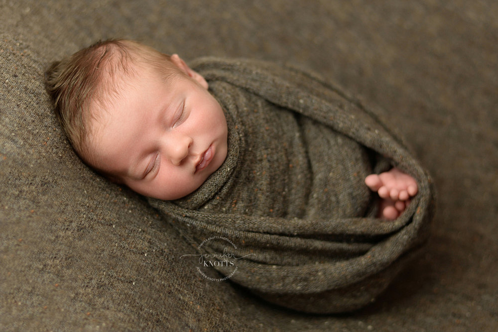 newborn baby wrapped in brown fabric sleeps during Wilmington nc newborn photography session