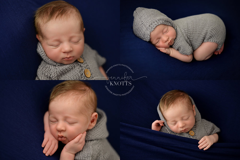 newborn baby boy dressed in gray romper sleeps on navy fabric