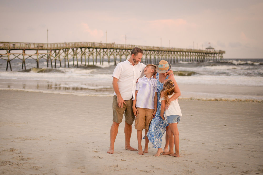 oak island photographer captures family embracing in front of pier