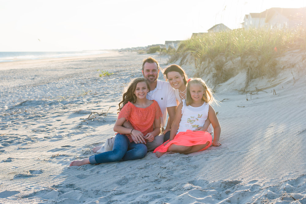 oak island photographer captures family sitting on beach during vacation