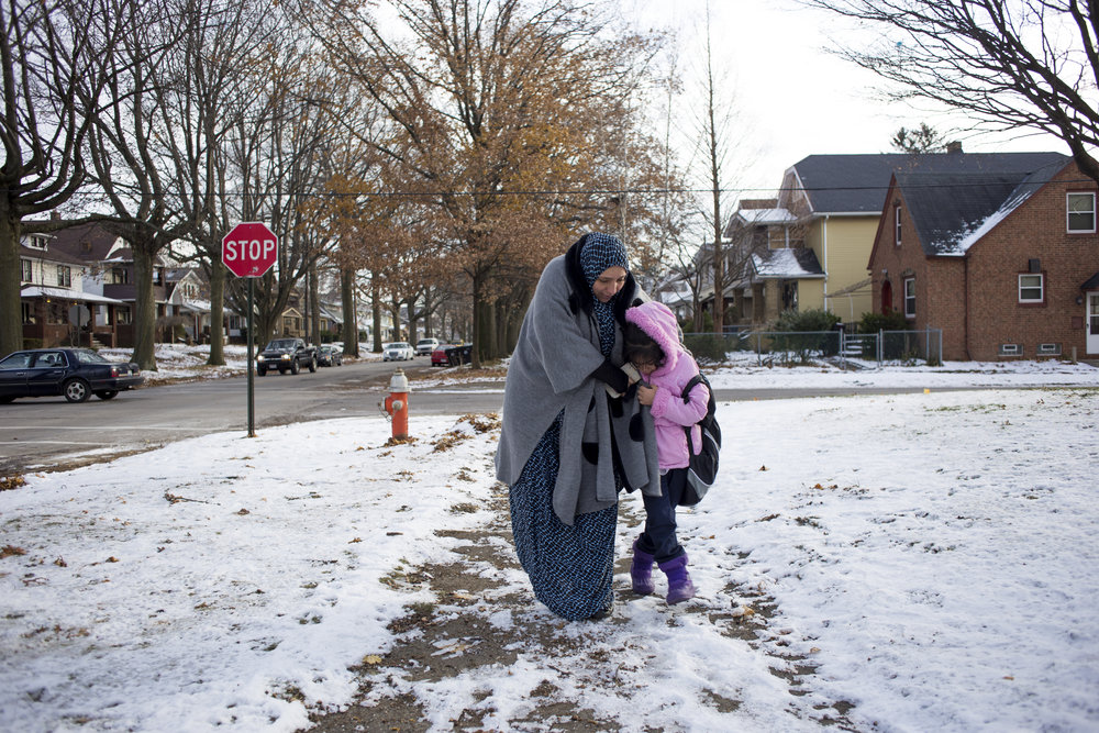 Mariam helps her daughter Baisan navigate the precarious and icy sidewalks as they walk home from the school bus.