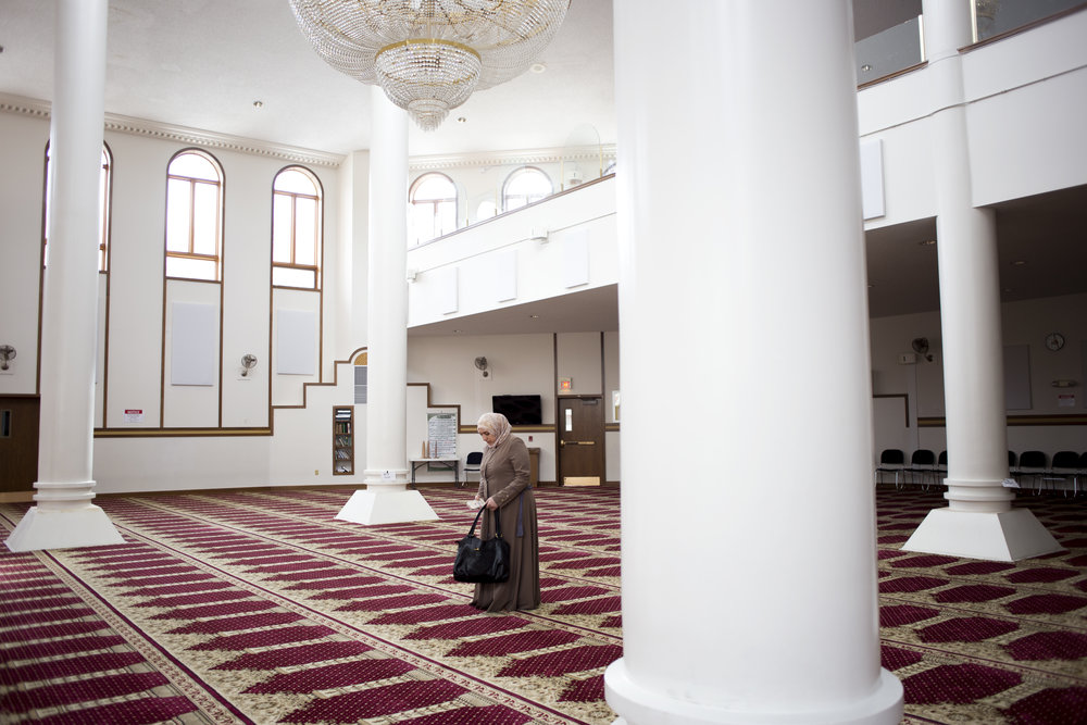 "Mariam visits the Islamic Center of Cleveland for the first time since she arrived in the States on Monday, Dec. 5, 2016. As she stepped into the prayer room, she stopped at a white pillar and looked up into the light for a moment. ""I'm really happy to see a mosque like this because in these four to five months, I haven't seen a mosque this beautiful,"" Mariam said."