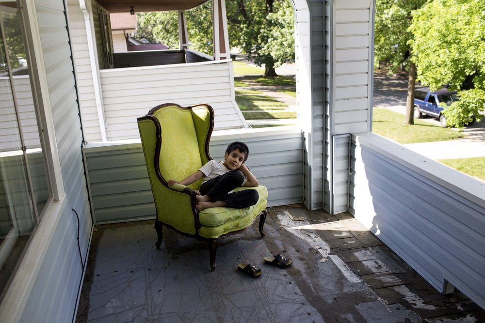 Adan, 6, relaxes on his families balcony.