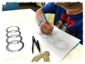 Riley applies geometry knowledge to draw car logos.