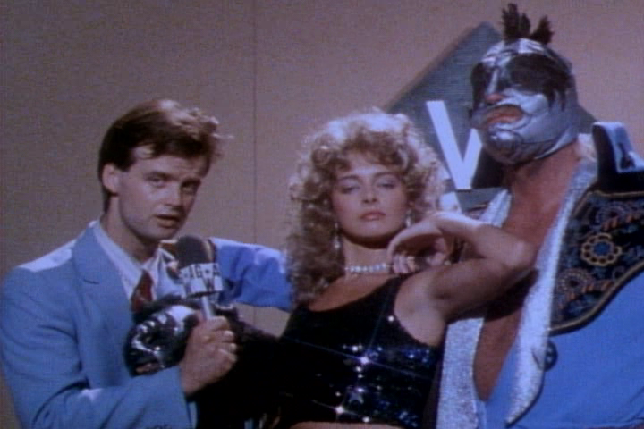 THE MASK (RIGHT) IS BELIEVED BY SOME WRESTLING PUNDITS TO BE MAD DOG JOE DE CURSO IN DISGUISE. THE MASK'S MANAGER, ANGEL FACE (LYDIE DENIER, CENTRE) SERVES AS HIS MOUTHPIECE, THUS FURTHER CONCEALING THE MASK'S TRUE IDENTITY