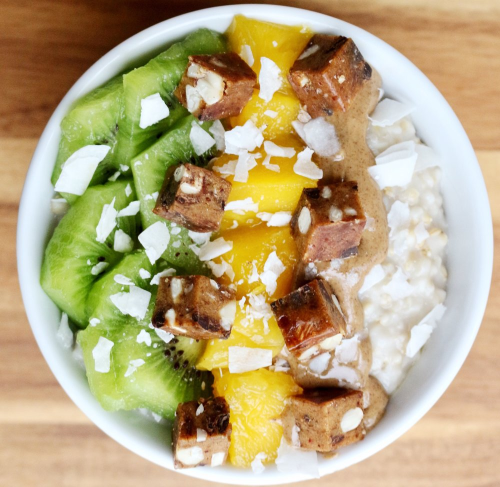 Coconut Oatmeal with almond butter, mango, kiwi, rx protein bar chunks and flaked coconut. Oatmeal: Bring 1 cup of coconut milk to a boil and add ½ cup oats. After cooking add a scoop of protein powder and a pinch of pink salt.
