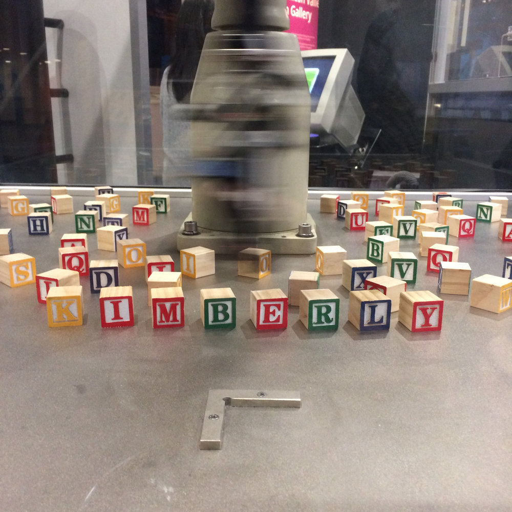 Robot programmed to spell out text entered into a computer with tangible, toy blocks.