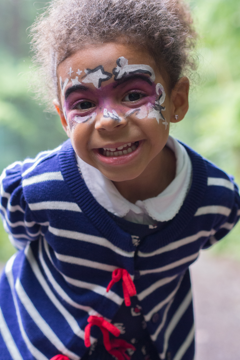 Smiling young girl with face paint at a party.