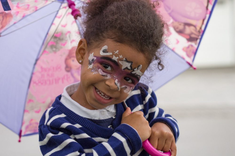 Smiling girl with face paint at a party in the DMV area.