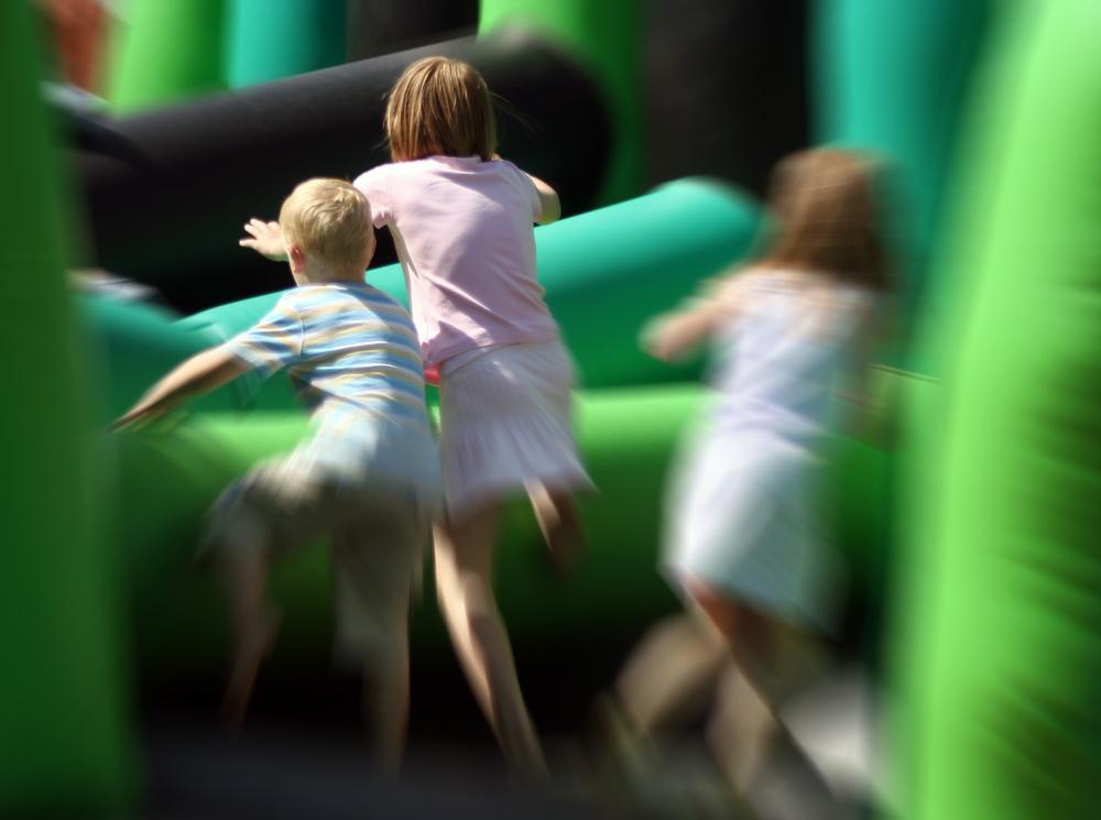 Children running towards a green moonbounce rental at a party.