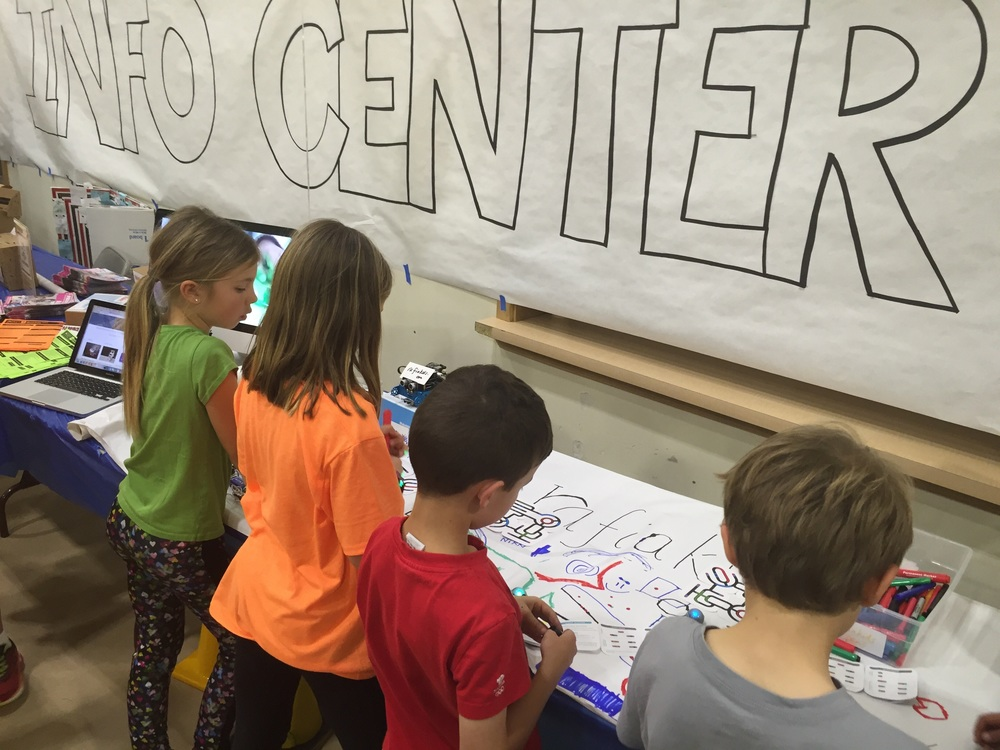 Elementary students taking a break from hands-on craft to program tiny ozobots at the rafiakids table