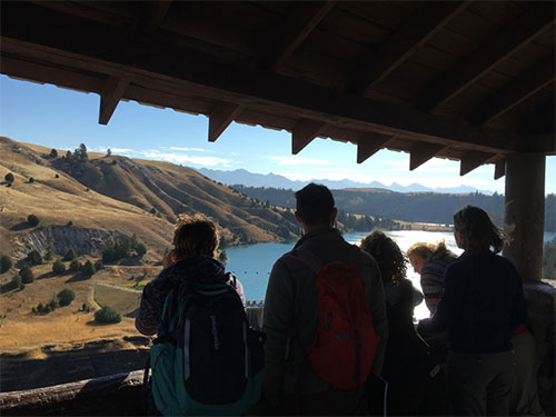 Andrea discusses the hydrology surrounding the dam with students, looking eastward toward the Mission mountains.