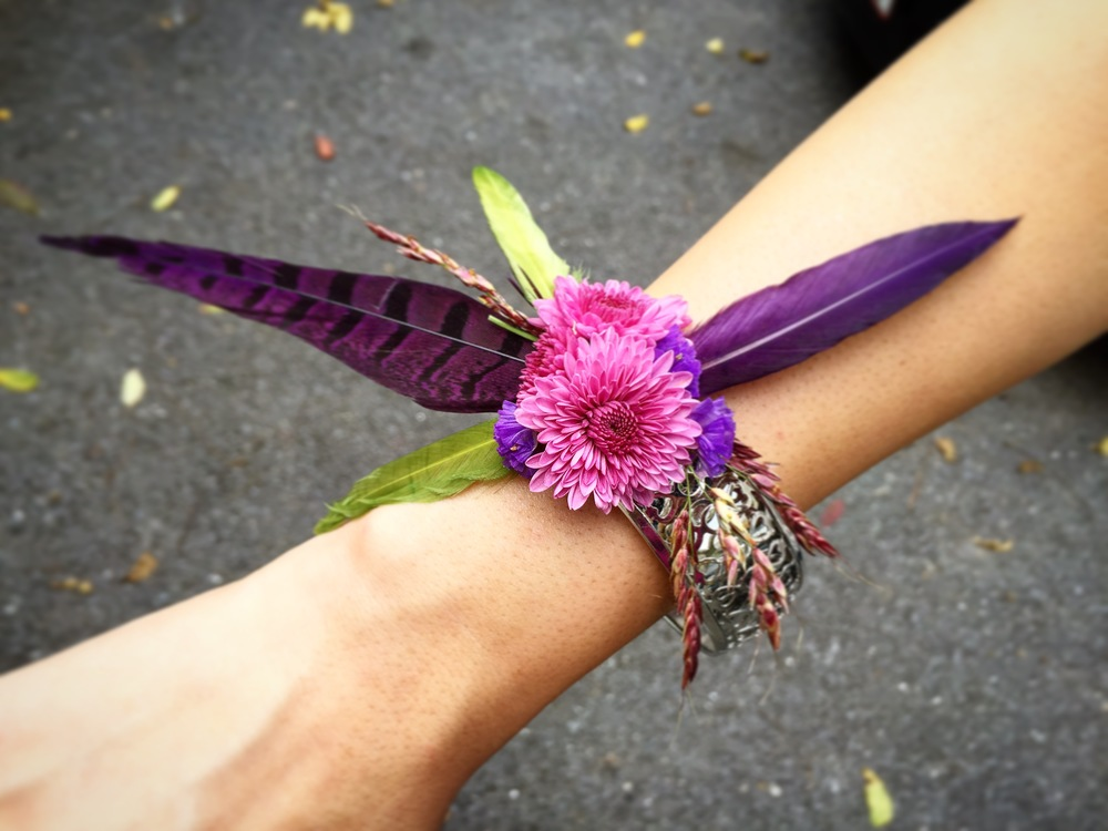 Floral Bracelet designed by Westvirjeni with purple pheasant feathers, dried grasses, and mums on a sterling silver bracelet.