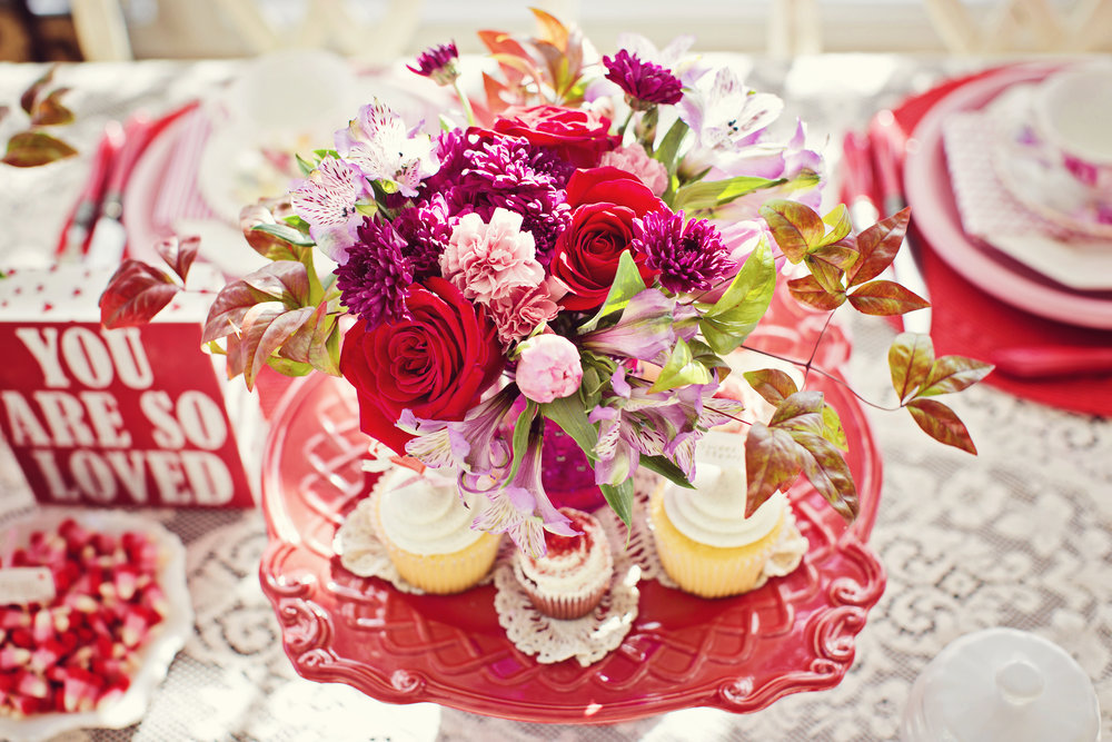 You are so Loved $55   Valentine's themed mixed arrangement in a keepsake container filled with red, pink, and purple blooms, including roses and other greenery.