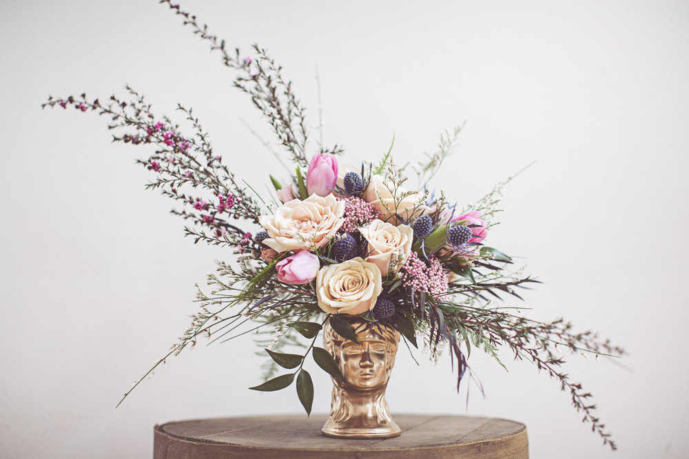 Head over Heels $75   Funky and feminine arrangement with roses and other blooms in a unique keepsake antique vase. Available in a classic (as seen above), moody (light to deep reds and purples), or tropical color palette.