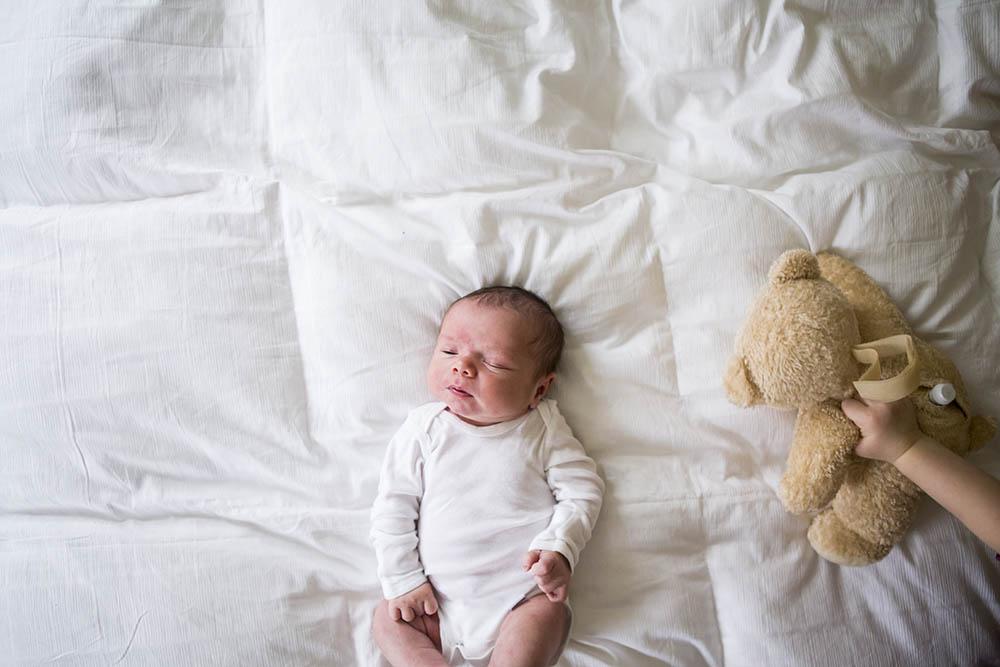 Big sister shows newborn brother a teddy bear