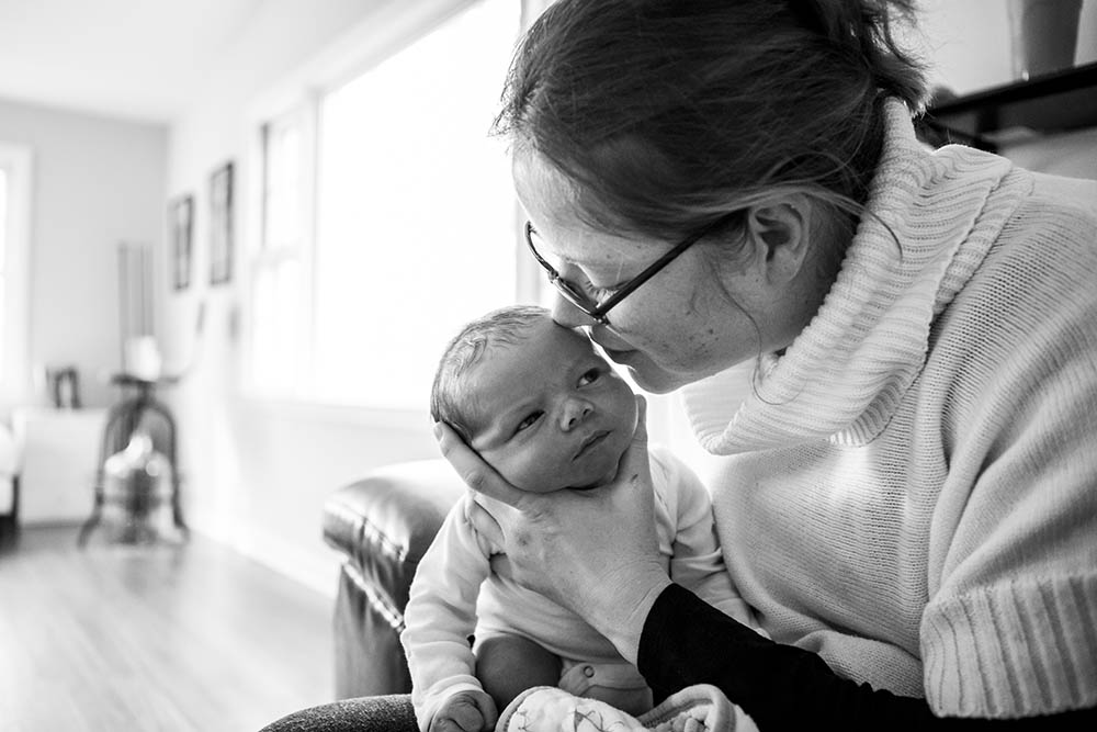 CT newborn nuzzled by mother in black and white photograph