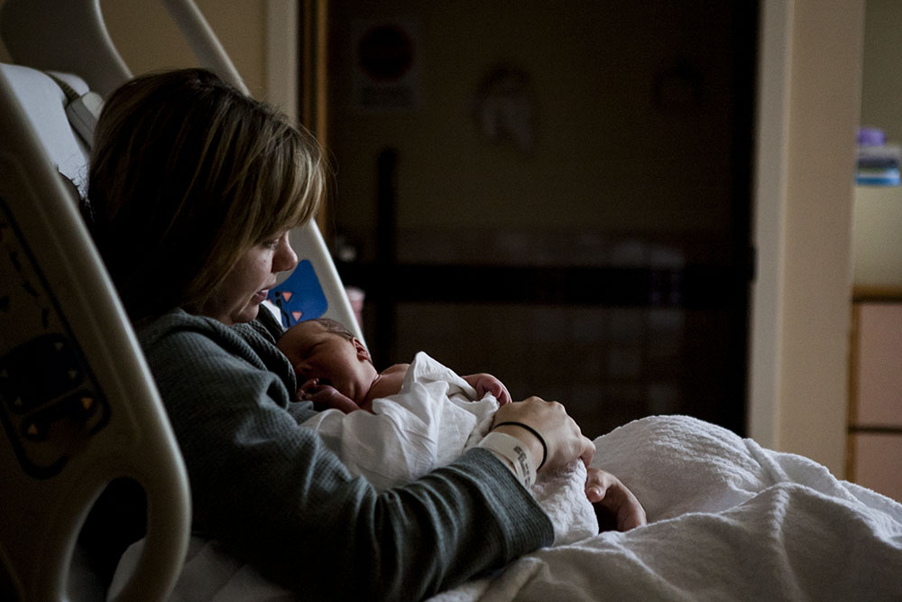 Mom holds newborn baby in hospital bed.