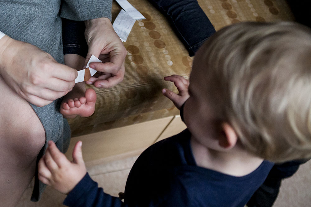 Family photography detail of my applying bandaid to toddler's foot while sibling watches.