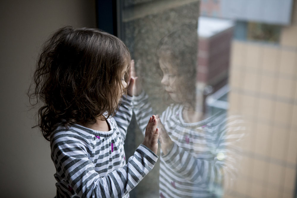 Girl looks out window with her reflection.